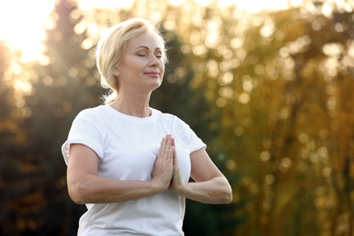 Mature woman practicing yoga outdoors in morning