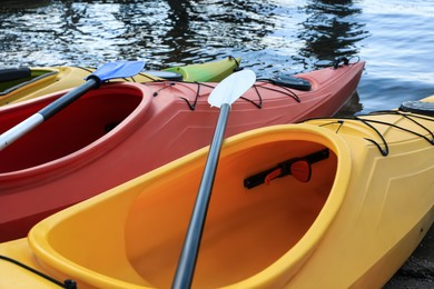Modern kayaks with paddles on river, closeup. Summer camp activity
