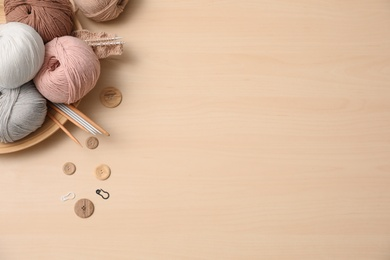 Flat lay composition with threads and crafting accessories on wooden table, space for text. Engaging hobby