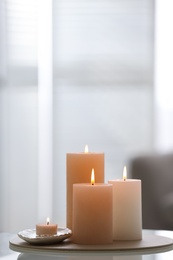 Burning candles on table indoors, space for text. Interior elements