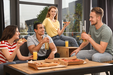 Group of friends having fun party with delicious pizza in cafe
