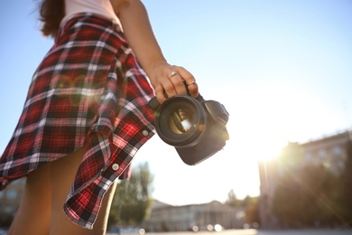 Young photographer with professional camera outdoors, closeup. Space for text