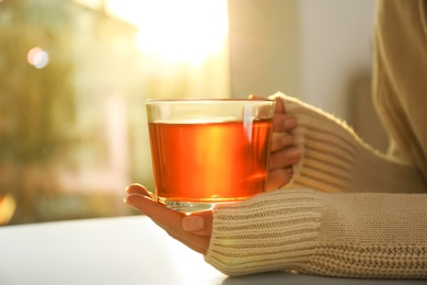 Woman holding glass cup of tea at table at home, closeup