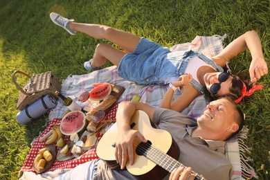Happy couple with guitar on picnic in park