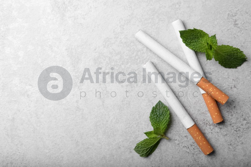 Menthol cigarettes and mint leaves on grey table, flat lay. Space for text