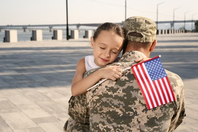 Soldier and his little daughter with flag of USA hugging outdoors, space for text