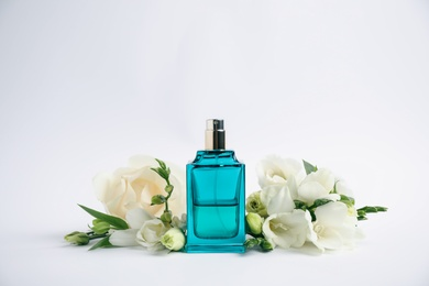 Bottle of perfume and beautiful flowers on white background