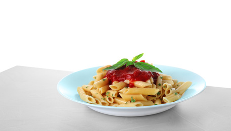 Tasty pasta with tomato sauce and basil on light grey table against white background
