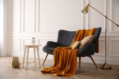 Comfortable sofa with knitted blanket, coffee table and lamp in stylish room interior