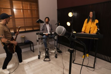 Music band performing in modern recording studio