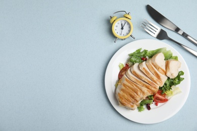 Plate of appetizing food, alarm clock and cutlery on light blue table, flat lay with space for text. Nutrition regime