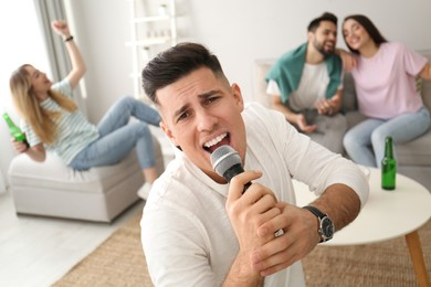 Man singing karaoke with friends at home