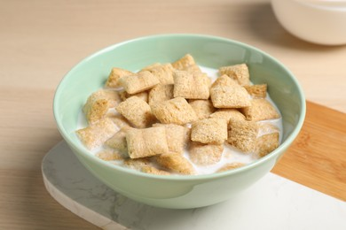 Bowl with tasty corn pads and milk on wooden table, closeup