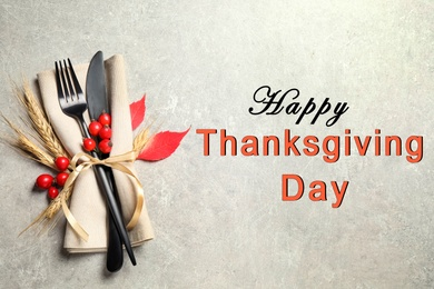 Happy Thanksgiving Day card. Cutlery, rosehip berries and napkin on light table, top view