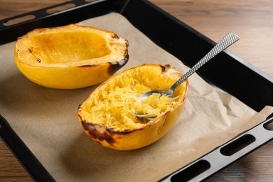 Baking sheet with halves of cooked spaghetti squash and spoon on wooden table, closeup
