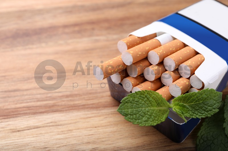 Pack of menthol cigarettes and mint leaves on wooden table, closeup. Space for text