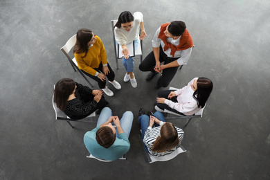 Psychotherapist working with patients in group therapy session, top view