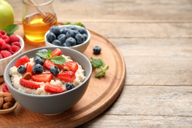 Tasty oatmeal porridge with berries and almond nuts served on wooden table, space for text