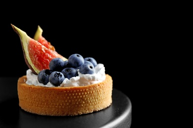 Tart with blueberries and figs on black table against dark background, space for text. Delicious pastries