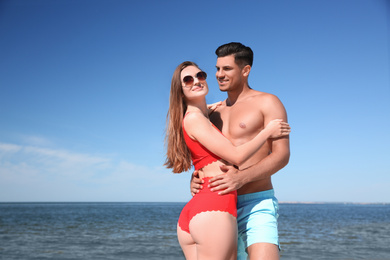 Beautiful woman and her boyfriend on beach. Happy couple