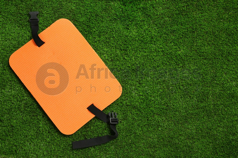 Orange foam tourist seat mat on green grass, top view. Space for text