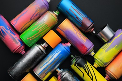 Used cans of spray paints on black background, flat lay. Graffiti supplies