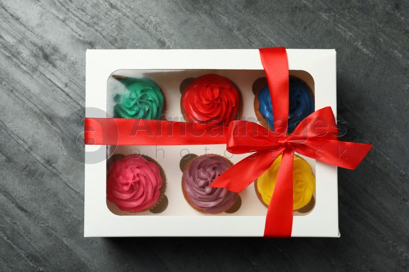 Box with different cupcakes on dark background, top view