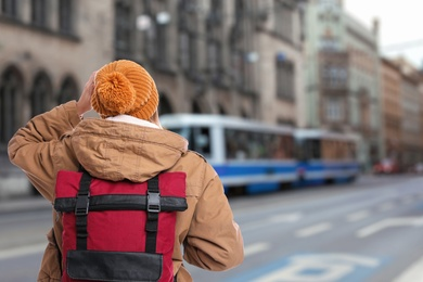Traveler with backpack in foreign city during vacation, back view