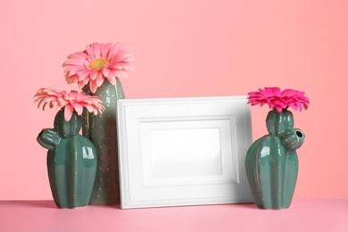 Decorative cacti, flowers and photo frame on table against color background, space for text. International Women's Day