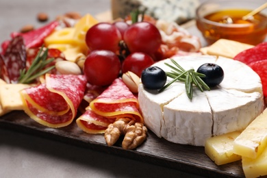 Wooden board with different appetizers on table, closeup
