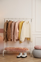 Rack with stylish warm clothes and shoes in modern dressing room