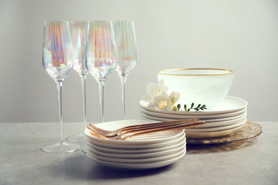 Set of glasses and dishes with flowers on light grey table
