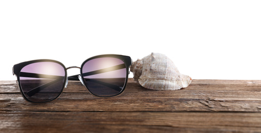 Stylish sunglasses and shell on wooden table against white background