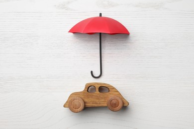 Small umbrella and toy car on white wooden background, flat lay