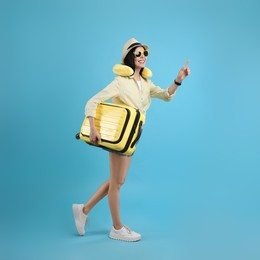 Happy female tourist with suitcase and travel pillow on light blue background