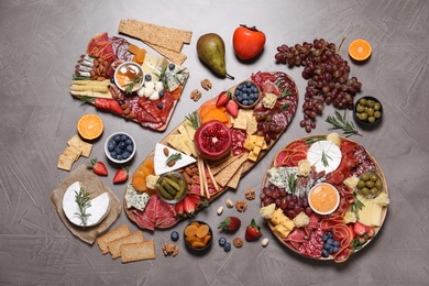 Wooden plates with different delicious snacks on grey table, flat lay