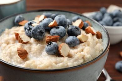 Tasty oatmeal porridge with blueberries and almond nuts in bowl on table, closeup