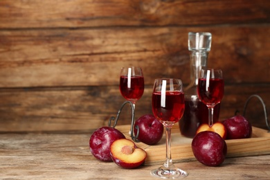 Delicious plum liquor and ripe fruits on wooden table. Homemade strong alcoholic beverage