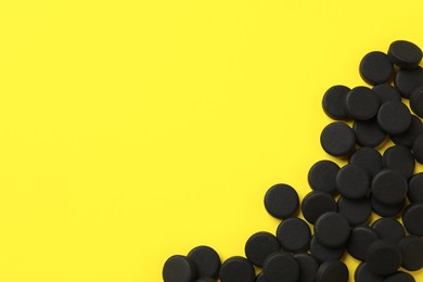 Activated charcoal pills on yellow background, flat lay with space for text. Potent sorbent