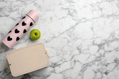 Thermos, lunch box and apple on white marble table, flat lay. Space for text