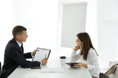 Office employees talking at table during meeting