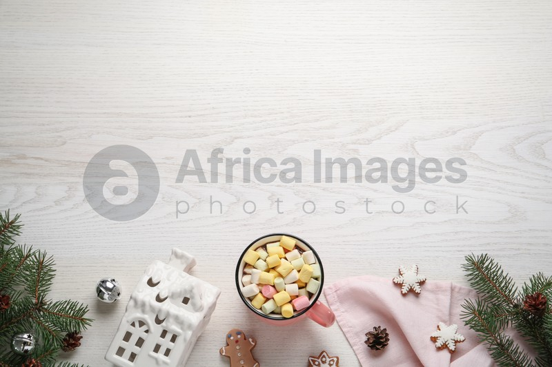 Delicious hot chocolate with marshmallows and Christmas decor on white wooden table, flat lay. Space for text