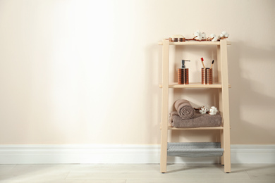 Wooden shelving unit with toiletries near beige wall indoors, space for text. Bathroom interior element