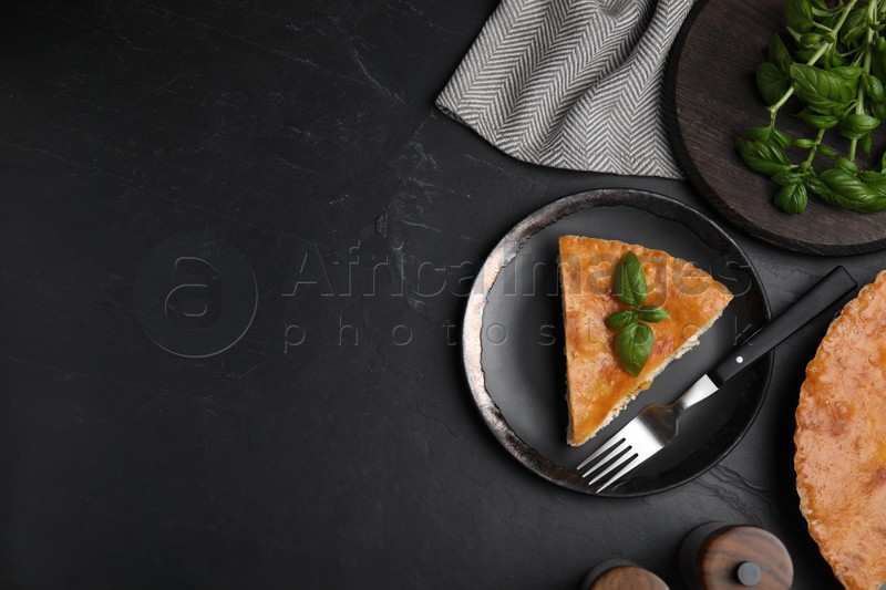 Piece of delicious pie with meat and basil on black table, flat lay. Space for text