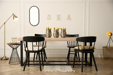 Stylish wooden dining table and chairs in room. Interior design