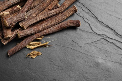 Dried sticks of liquorice root on black table, flat lay. Space for text