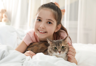 Cute little girl with cat lying on bed at home. First pet
