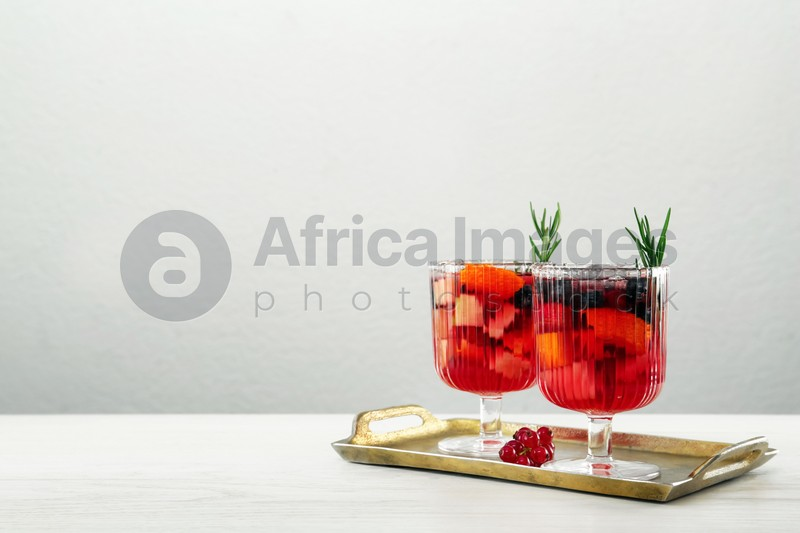 Glasses of Red Sangria on white wooden table against light grey background. Space for text