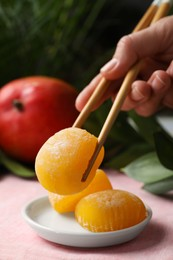 Woman eating delicious mochi with chopsticks at table, closeup. Traditional Japanese dessert