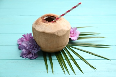 Young peeled coconut with straw, palm leaf and flowers on light blue wooden table